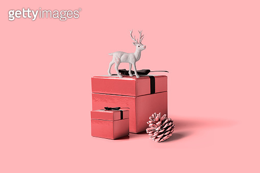 Christmas gift box with a white reindeer on pink background, minimal composition
