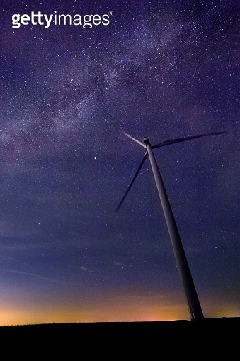 One wind turbine with beautiful milky way in background with bright stars over flat land at midnight