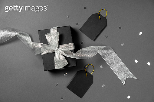 Gift box wrapped in black paper with silver ribbon, stars confetti and price tags on gray background. Copy space and top view. Black friday box gift present isolated.