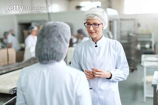 Smiling blonde woman in white sterile uniform and with eyeglasses talking to her boss while standing in food plant.