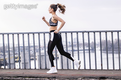 Sports woman in motion jogging over bridge