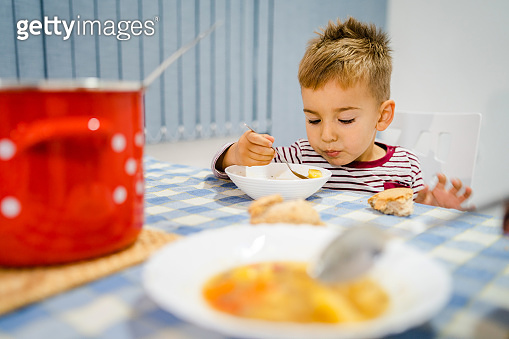 Small little boy eating having lunch or dinner by the table at home sitting by the plate using spoon having bread and meal or soup