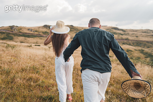 Young couple in love on the mountain range in summer or autumn day walking in nature freedom she is holding his hand and leading wearing hat back view
