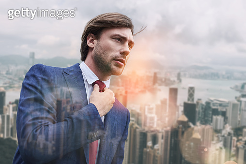 Busy morning. Attractive business expert adjusting his necktie while standing outdoors with cityscape on the background