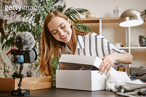What is inside? Cute female blogger opening a box and smiling while recording new video review for her vlog
