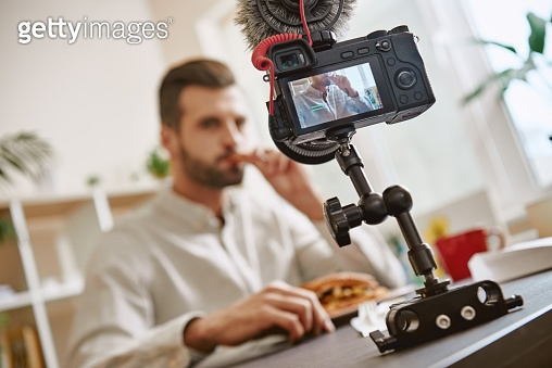 Tasting. Close up of digital camera screen with male food blogger tasting sandwich while recording new video for his vlog.