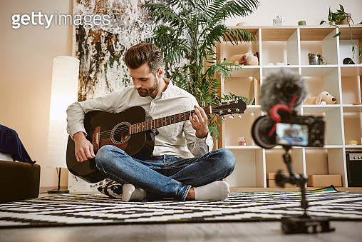 My inspiration. Bearded male music blogger sitting on the floor and holding the guitar, while recording new video for his vlog