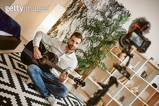 More subscribers. Bearded male music blogger sitting on the floor and holding the guitar, while recording new video for vlog