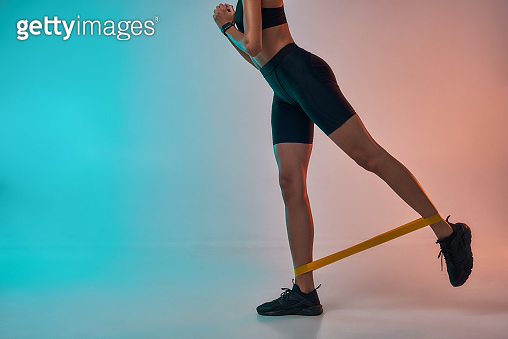 Perfect buttocks. Cropped photo of athlete woman in sports clothing exercising with a resistance band while standing in studio against colorful background