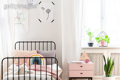 Bright child bedroom with colorful bedding, prints on the wall and pastel pink bedside table, real photo