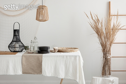 Close-up of table with white linen tablecloth and beige napkin