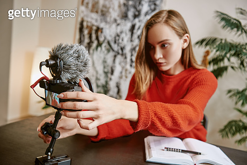 I'm almost ready... Portrait of serious female blogger setting up her tripod mounted digital camera before making a new video for vlog