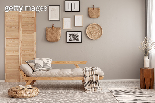 Scandinavian beige futon with patterned pillows and blanket in natural style living room interior