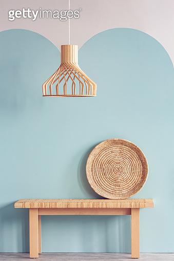 Wicker chandelier above wooden bench in bright living room interior