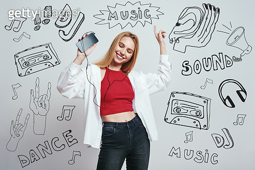 Time for music. Close up portrait of young woman in casual wear listening music with her smart phone, dancing and smiling while standing against grey background with music theme doodles