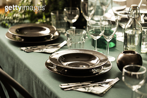 Close-up of a dark dining set on an elegant table with green cloth in a restaurant interior. Real photo