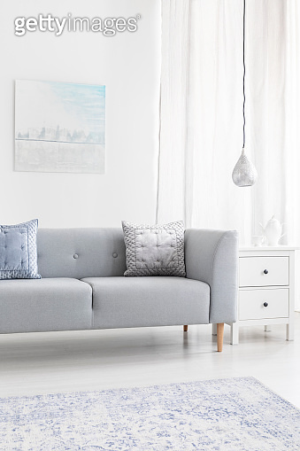 Grey sofa with cushions near lamp in minimal living room interior with poster and carpet. Real photo