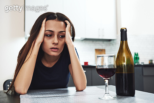 It'u2019s gonna get harder before it gets easier. But it will get better, you just gotta make it through the hard stuff first. Drunk girl looking at bottle of alcohol. Soccial issue alcoholism.