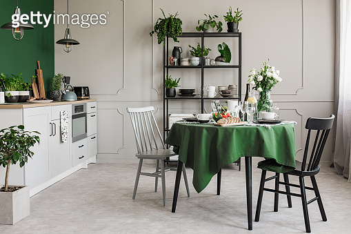 Elegant grey and green kitchen with breakfast on round dining room table