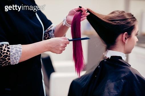 Hairdresser combing woman customer hair