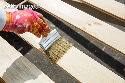 Painter holding a paintbrush over wooden surface, protecting wood for exterior influences and weathering. Carpentry, wood treatment, hard at work, home improvement, do-it-yourself concept.