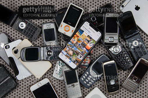 Modern smartphone on a pile of old, obsolete mobile phones