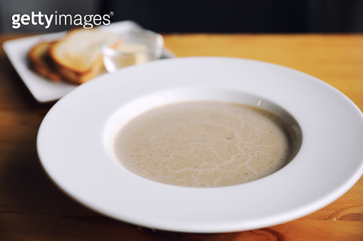 Apptetizer mushroom soup with bread on wood background