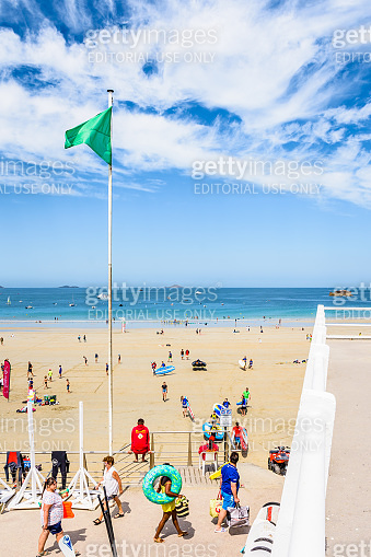 The green flag blows in the wind on the busy beach of Trestraou in Perros-Guirec, Brittany, France.