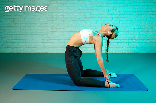 Handsome young slim gymnast woman in sports clothing stretching on brick wall in neon lights. Flexible muscular woman doing gymnastic and yoga exercises.