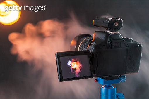 Photo of camera on a blue tripod that photographs in the studio a professional lighting device in the smoke. Studio lights and smoke equipment. Camera with radio synchronizer