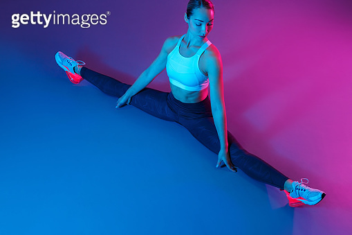 Attractive young slim gymnast woman in sports clothing stretching on the floor in neon lights. Flexible muscular woman doing gymnastic and yoga split.