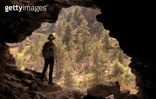 ADVENTURER WITH HAT AND BACKPACK IN A CAVE IN FRONT OF A PINE FOREST