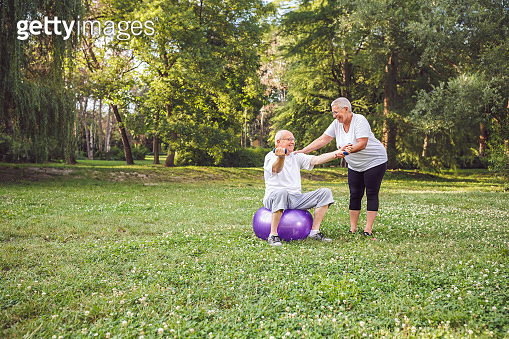 cardio exercise for senior- Happy senior woman with fitness balls in park