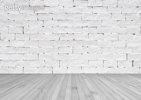 Grunge old aged brick wall painted in white color with wooden floor textured background in light grey
