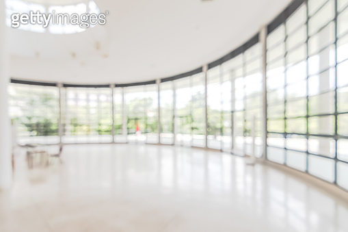 Hotel or office building lobby blur background interior view toward reception hall, modern luxury white room space with blurry corridor and building glass wall window