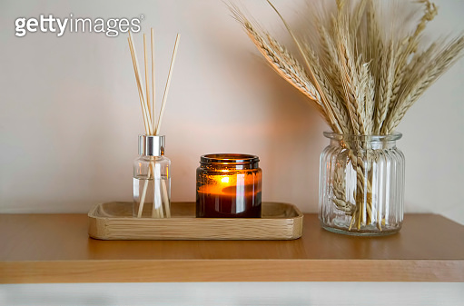 Home decoration. Shelf decor with candle, aroma diffuser and wheat ears in a vase, lifestyle interior details decor