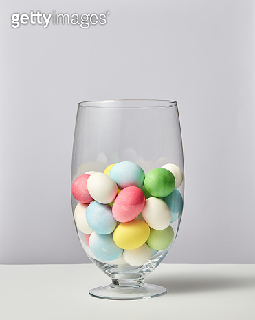 Glass vase with lots of small painted eggs on a gray background with copy space. Easter card layout
