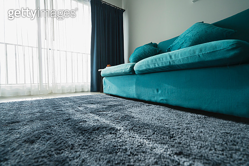 close up blue sofa and fur carpet rug near window family room interior background