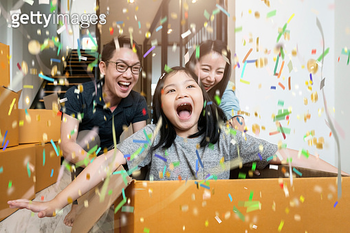 happiness asian family mom dad daughter moving in new house hand carry box of stuff with exited and fun cheerful expression