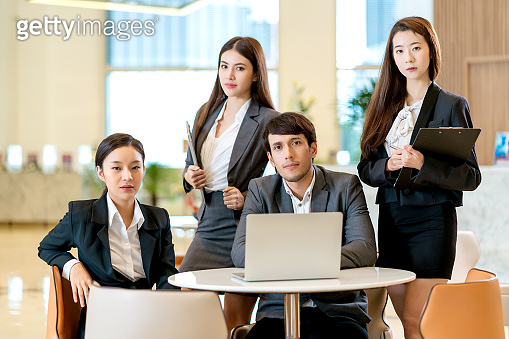 group of smart business asian teamwork business uniform look camera with confident and cheerful with modern design office background