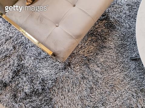 close up armchair gold brass leg on carpet rug living room