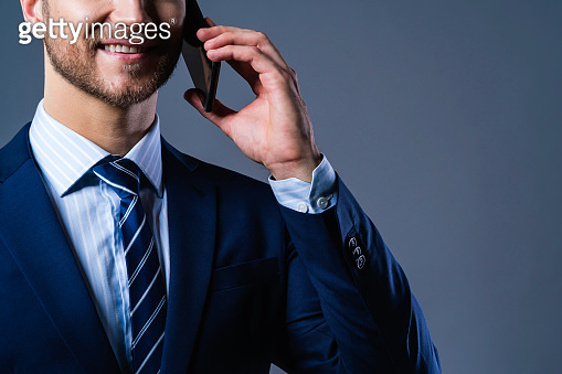 caucasian Successful businessman with beard close up mouse lip hand hold smartphone grey background