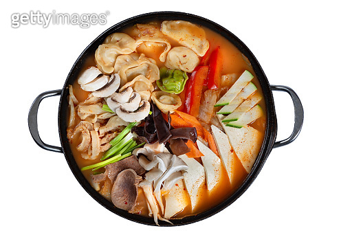 Pan of korean soup with kimchi, dumplings, beef and vegetables isolated