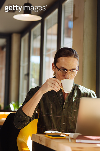 Pleasant nice man drinking coffee during his work