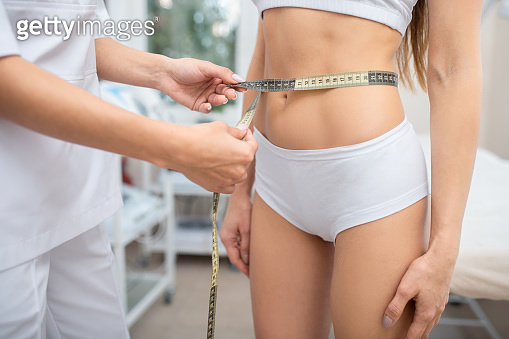 Woman wearing panties coming to diet specialist measuring her waist