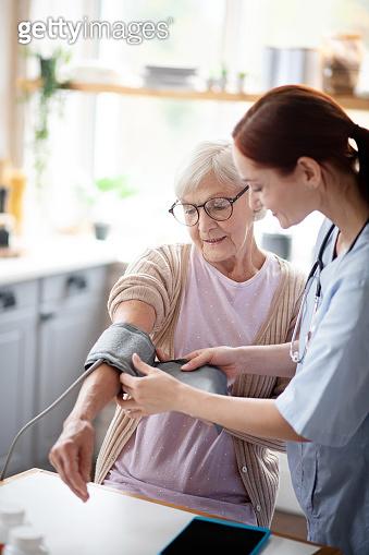 Retired woman watching nurse measuring blood pressure