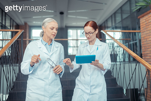 Female doctors in white coats on the stairs