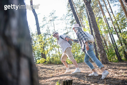Husband holding hand of wife while hiking in forest together