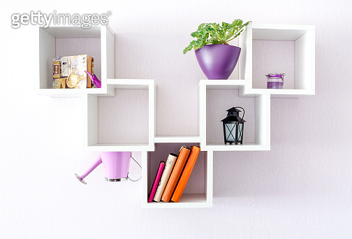 A modern white bookshelf on a white wall with a few things and a flower. Minimalism style.