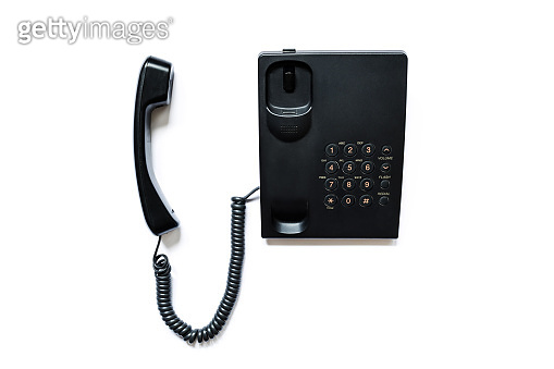 Simple modern push-button telephone of black color with a picked up handset isolated on a white background